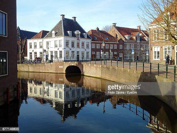 buildings by canal against sky - amersfoort netherlands stock photos and pictures