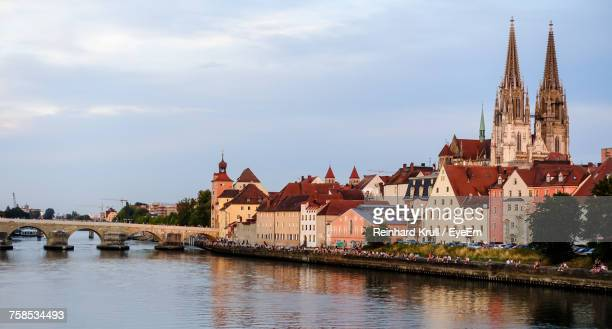 buildings by danube river against sky during sunset - regensburg stock photos and pictures