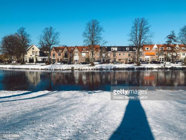buildings by frozen lake against sky during winter - bortes stock pictures, royalty-free photos & images
