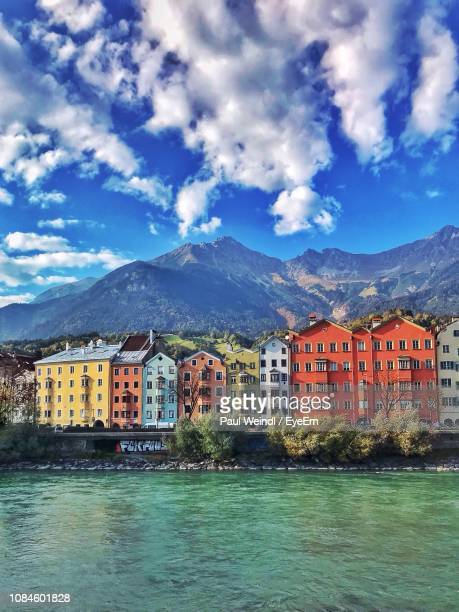 buildings by houses against sky - innsbruck stock pictures, royalty-free photos & images