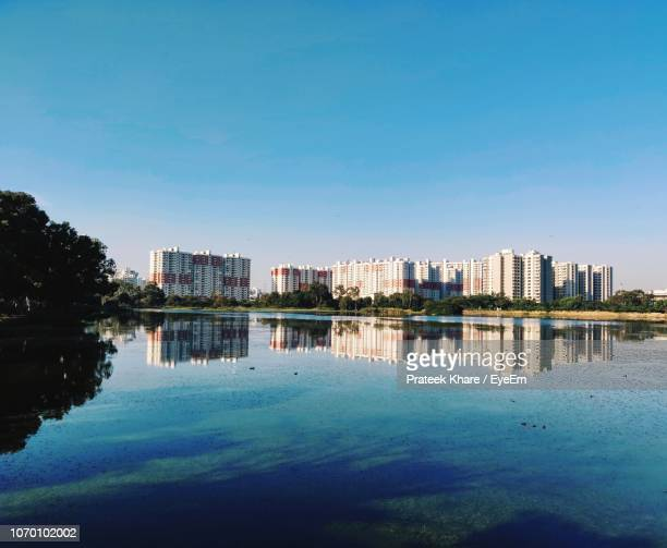 buildings by lake against blue sky - bangalore stock pictures, royalty-free photos & images