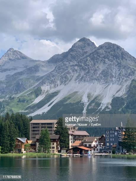 buildings by lake against mountains - アロサ ストックフォトと画像