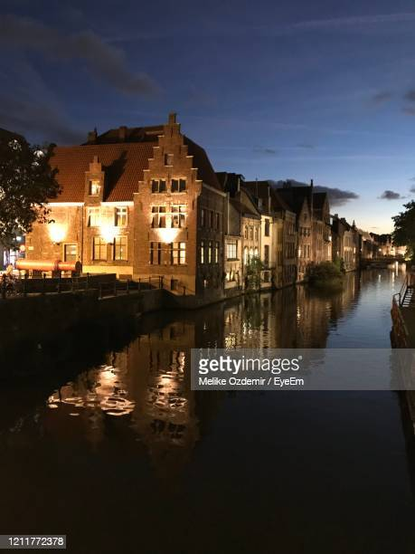 buildings by lake against sky in city at night - melike stock pictures, royalty-free photos & images
