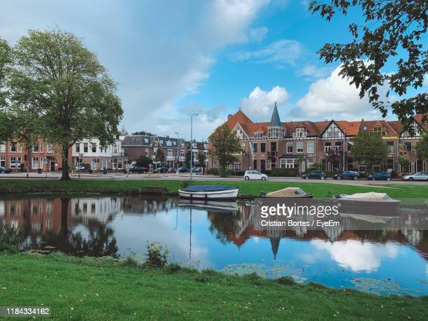 buildings by lake against sky in city - bortes stock photos and pictures