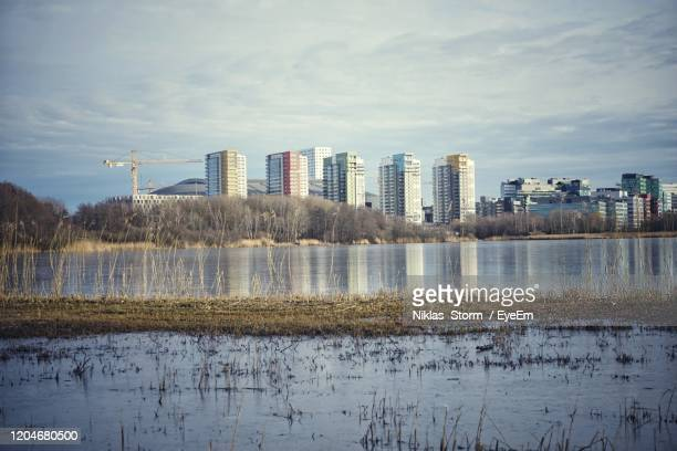 buildings by lake against sky in city - ソルナ ストックフォトと画像