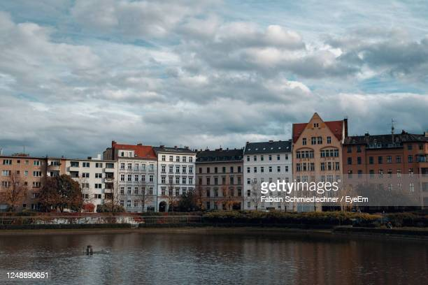 buildings by lake against sky in city - berlin stock pictures, royalty-free photos & images