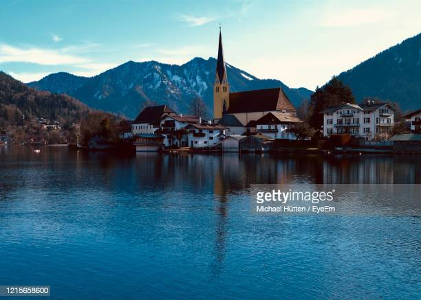 buildings by lake against sky - tegernsee stock pictures, royalty-free photos & images