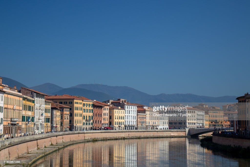 Buildings By River Against Clear Blue Sky : Stock Photo