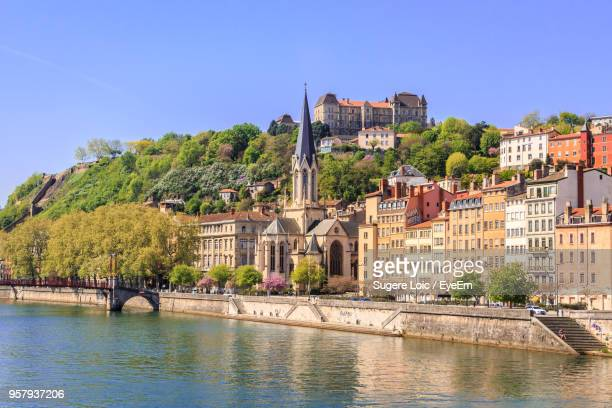 buildings by river against clear blue sky - lione foto e immagini stock