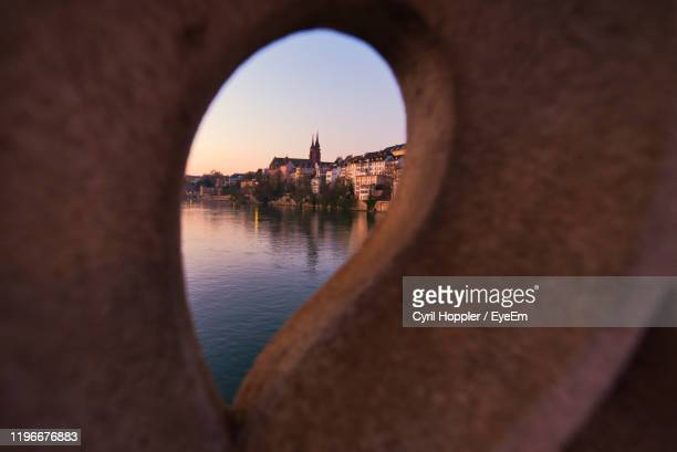 buildings by river against clear sky at sunset seen through hole - bazel stockfoto's en -beelden