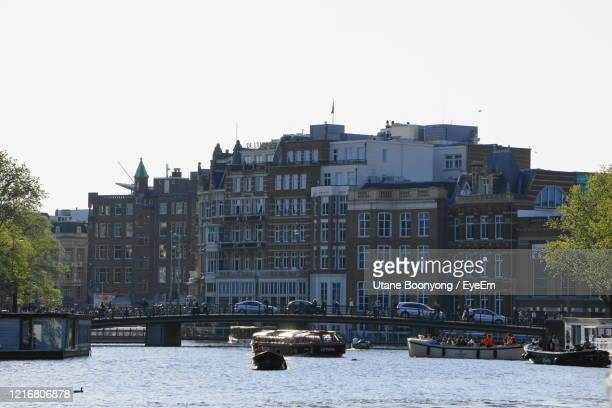 buildings by river against clear sky in city - history museum stock pictures, royalty-free photos & images