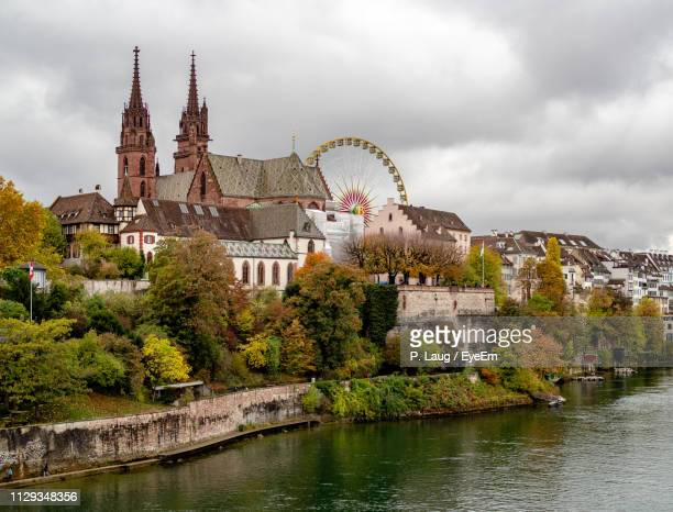 buildings by river against cloudy sky - basel switzerland stock pictures, royalty-free photos & images