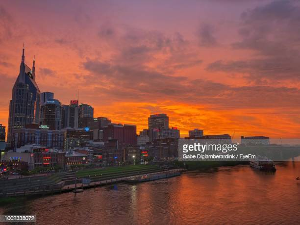 buildings by river against sky during sunset - 尖り屋根 ストックフォトと画像