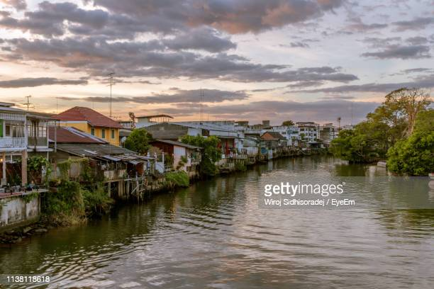 buildings by river against sky during sunset - chanthaburi stock pictures, royalty-free photos & images
