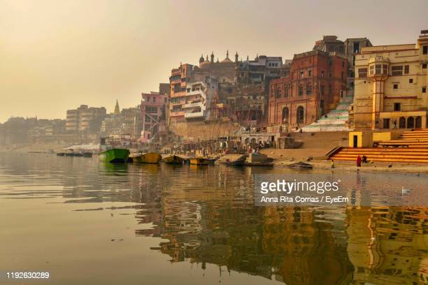 buildings by river against sky during sunset - river ganges stock pictures, royalty-free photos & images