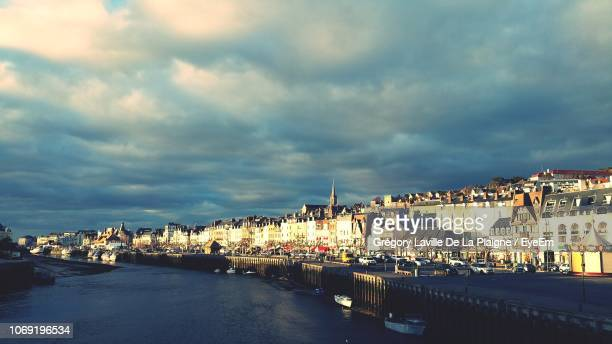 buildings by river against sky in city at dusk - trouville sur mer stock pictures, royalty-free photos & images