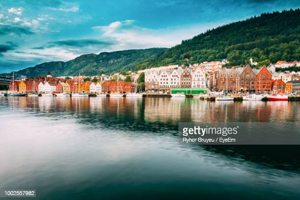 buildings by river against sky in city - bergen norway stock pictures, royalty-free photos & images