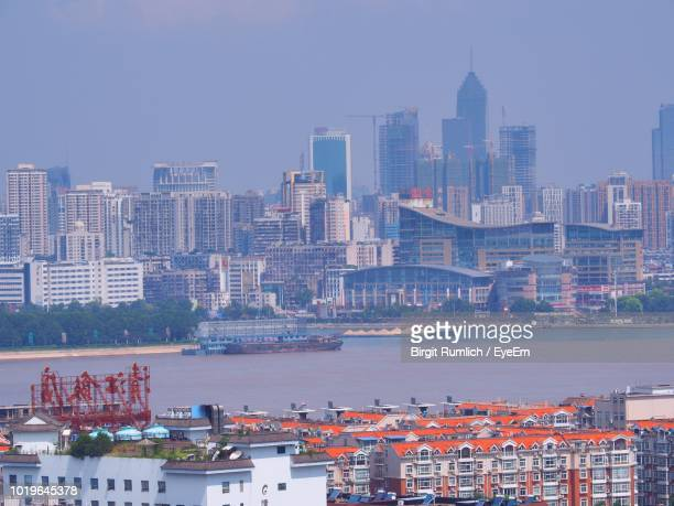 buildings by river against sky in city - wuhan stock photos and pictures