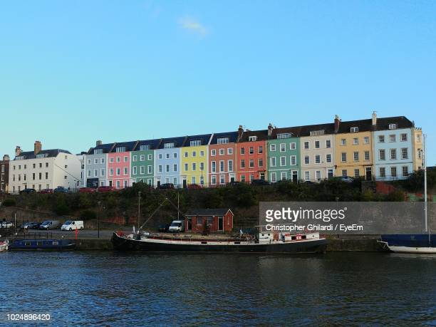 buildings by river against sky in city - bristol stock photos and pictures