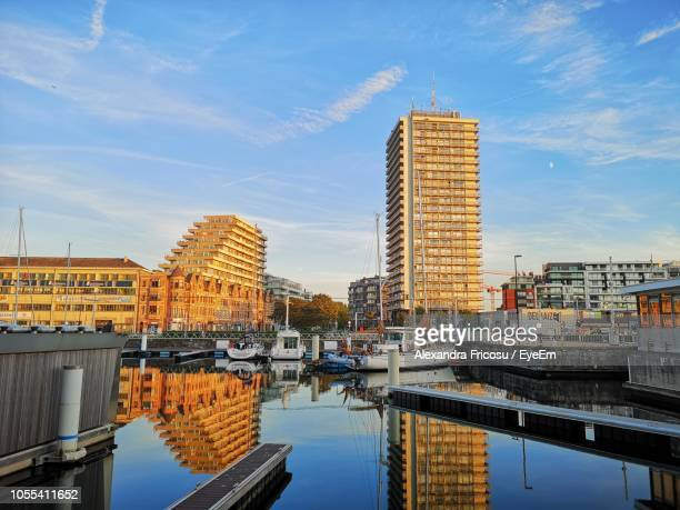buildings by river against sky in city - オステンド ストックフォトと画像