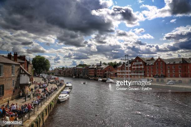 buildings by river against sky in city - york stock photos and pictures