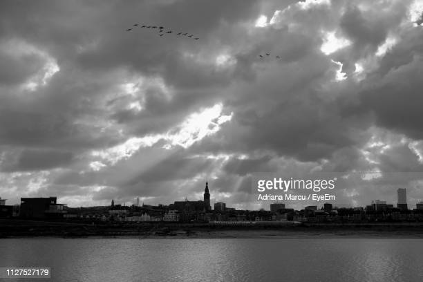 buildings by river against sky in city - nijmegen stock pictures, royalty-free photos & images