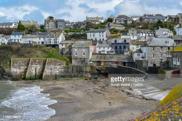 buildings by river against sky in city - port isaac stock pictures, royalty-free photos & images