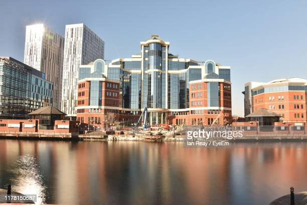 buildings by river against sky in city - waterfront stock pictures, royalty-free photos & images