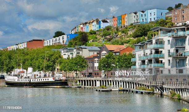 buildings by river against sky in city - bristol stock pictures, royalty-free photos & images