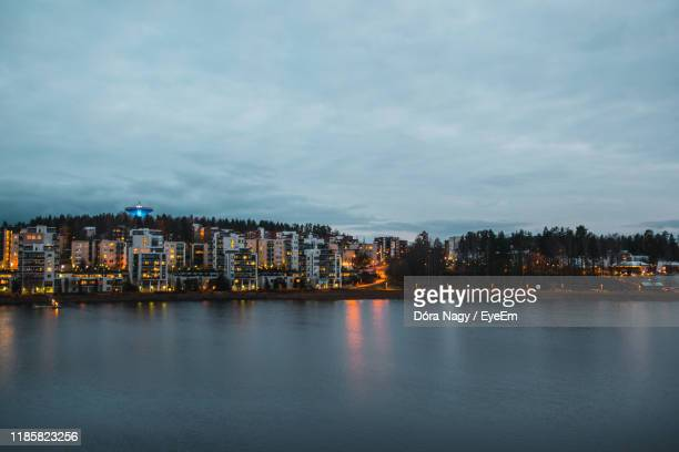 buildings by river against sky in city - jyväskylä stock pictures, royalty-free photos & images