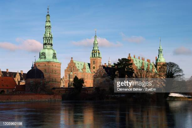 buildings by river against sky in city - hillerod stock pictures, royalty-free photos & images