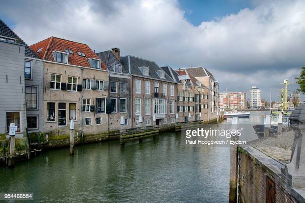 buildings by river against sky in city - hoogeveen stock pictures, royalty-free photos & images