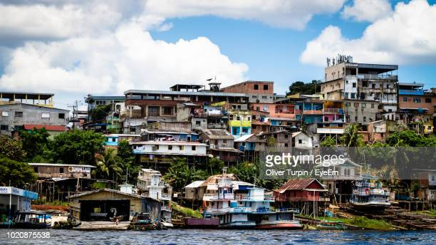 buildings by river against sky - manaus stock pictures, royalty-free photos & images