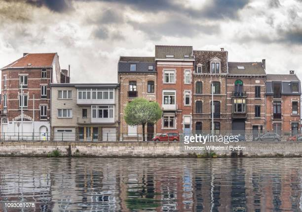 buildings by river against sky - liege province stock pictures, royalty-free photos & images