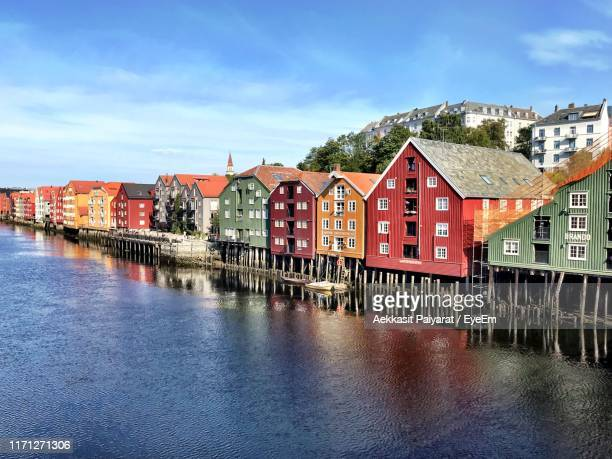 buildings by river against sky - trondheim stock pictures, royalty-free photos & images