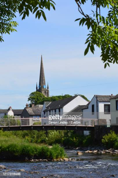 buildings by river against sky - cockermouth stock pictures, royalty-free photos & images
