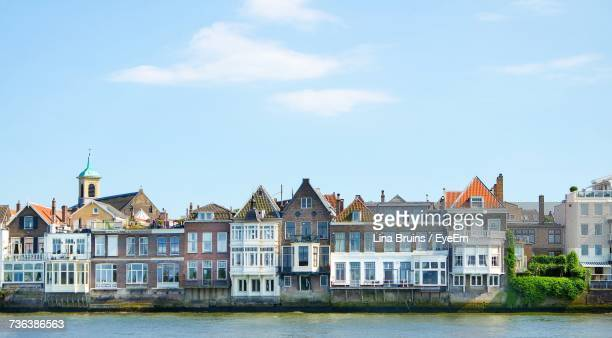 buildings by river against sky - dordrecht stock pictures, royalty-free photos & images