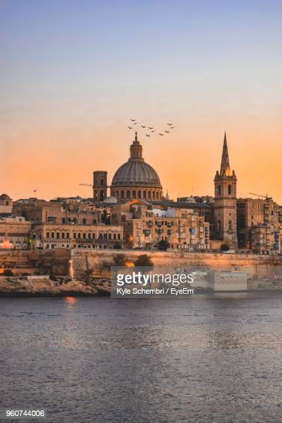 buildings by river during sunset - valletta stock pictures, royalty-free photos & images