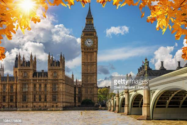 buildings by river in city against sky - westminster bridge stock pictures, royalty-free photos & images