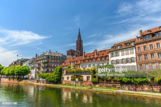 buildings by river in city - strasbourg stock pictures, royalty-free photos & images