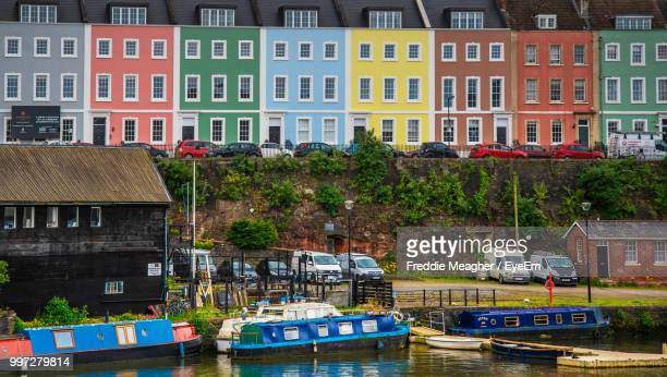 buildings by river in city - bristol stock photos and pictures
