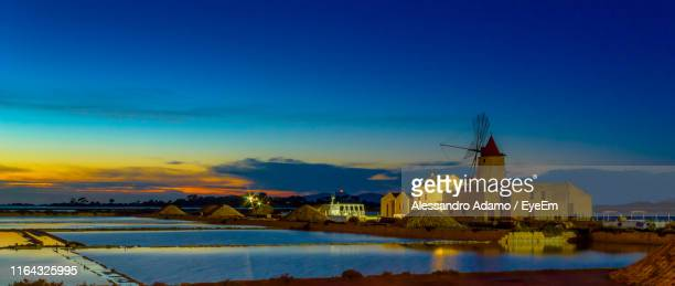 buildings by salt flats against sky during sunset - marsala sicily stock pictures, royalty-free photos & images