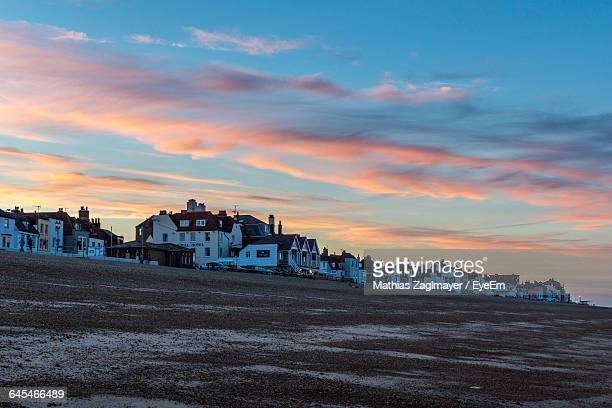 buildings by sandy beach against sky during sunset in city - deal england stock photos and pictures