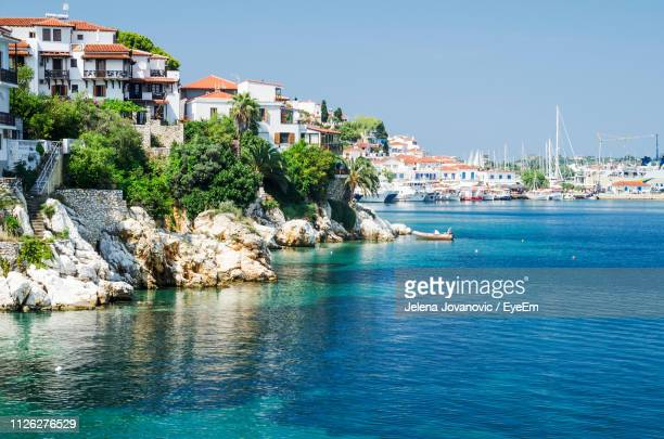 buildings by sea against clear blue sky - quayside stock photos and pictures