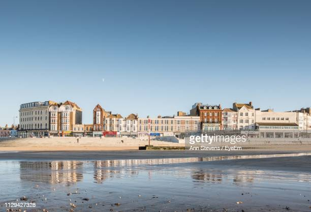 buildings by sea against clear blue sky - kent england stock pictures, royalty-free photos & images