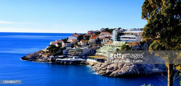 buildings by sea against clear blue sky - ljubomir belic stock pictures, royalty-free photos & images