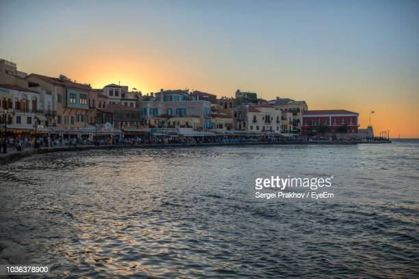 buildings by sea against clear sky at sunset - sergei stock pictures, royalty-free photos & images