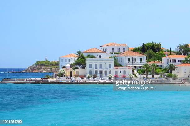 buildings by sea against clear sky - spetses stock pictures, royalty-free photos & images