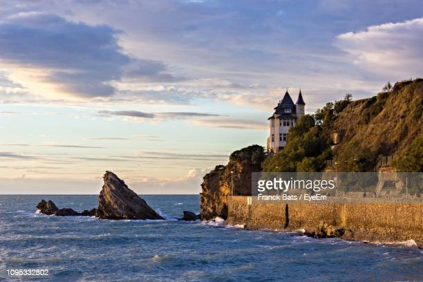 buildings by sea against cloudy sky - biarritz stock pictures, royalty-free photos & images