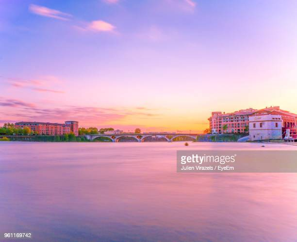 buildings by sea against sky at sunset - toulouse stock pictures, royalty-free photos & images